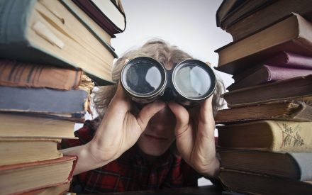 Woman looking through binoculars crouched between two stacks of books.